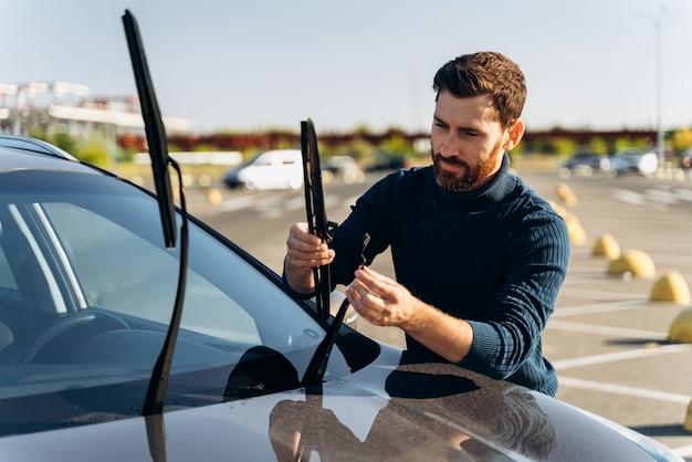 Mężczyzna zmienia wycieraczki w samochodzie, stojąc na ulicy. mężczyzna wymienia wycieraczki przedniej szyby w samochodzie. zmień koncepcję wycieraczek samochodowych