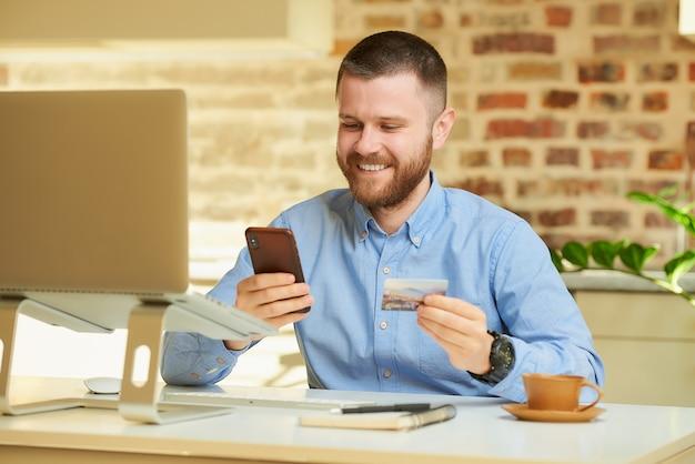 Mężczyzna znajduje sklep internetowy na smartfonie z kartą kredytową w dłoni przed komputerem w domu