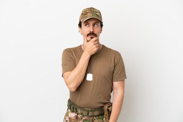 Mężczyzna żołnierz na białym tle mający wątpliwości i zdezorientowany wyraz twarzy