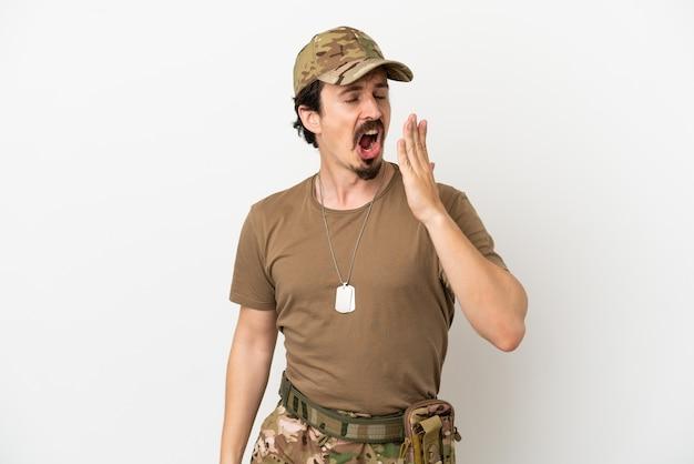 Mężczyzna żołnierz na białym tle ziewa i zakrywa ręką szeroko otwarte usta