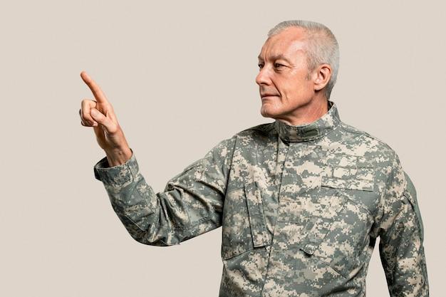 Mężczyzna żołnierz naciskający palec wskazujący na niewidzialnym ekranie