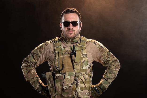 Mężczyzna żołnierz w kamuflażu na ciemnej ścianie