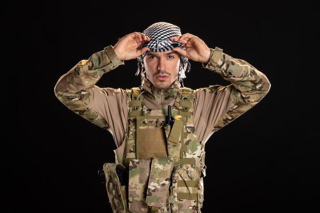 Mężczyzna żołnierz w kamuflażu na czarnej ścianie