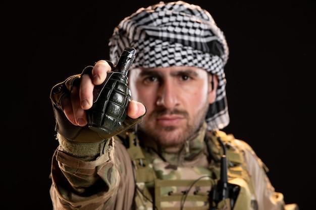 Mężczyzna żołnierz w kamuflażu trzymający granat na czarnej ścianie