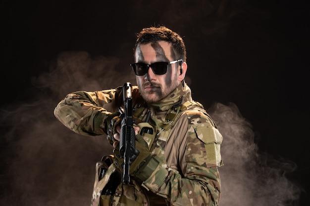 Mężczyzna żołnierz w kamuflażu trzymający karabin maszynowy na ciemnej ścianie