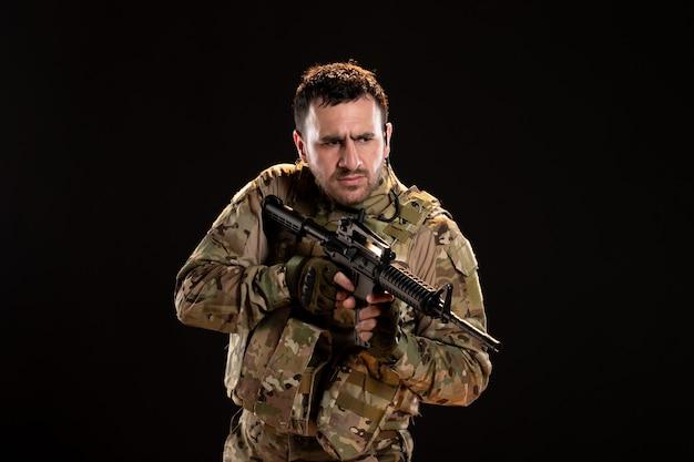 Mężczyzna żołnierz w kamuflażu trzymający karabin maszynowy na czarnej ścianie