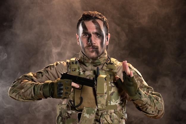Mężczyzna żołnierz w kamuflażu trzymający pistolet na zadymionej ciemnej ścianie