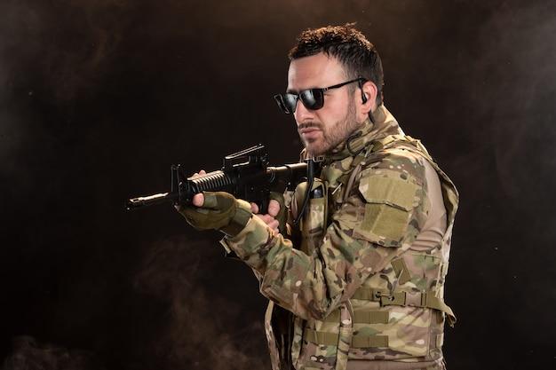 Mężczyzna żołnierz w kamuflażu z karabinem maszynowym na ciemnej ścianie