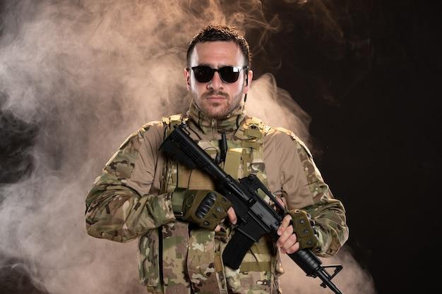 Mężczyzna żołnierz w kamuflażu z karabinem maszynowym na ciemnej zadymionej podłodze wojownik czołg wojskowy