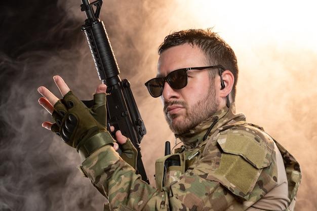 Mężczyzna żołnierz w kamuflażu z karabinem maszynowym na zadymionej ścianie