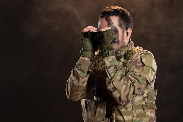 Mężczyzna żołnierz w mundurze wojskowym z lornetką na ciemnej ścianie