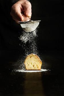 Mężczyzna zraszania cukrem pudrem na ciastko na ciemnym tle
