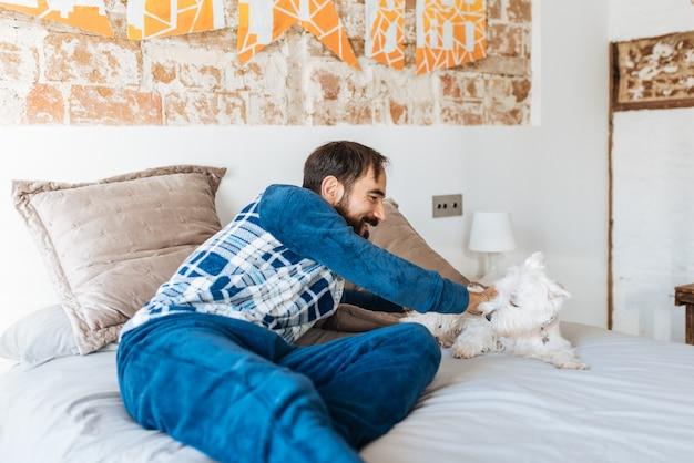Mężczyzna zrelaksowany w domu, siedząc w łóżku ze swoim psem