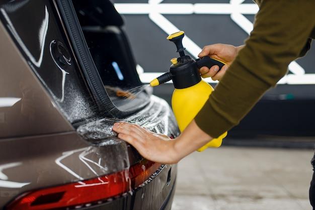 Mężczyzna zwilża powierzchnię tylnego zderzaka samochodu sprayem przed nałożeniem folii ochronnej. montaż powłoki chroniącej lakier samochodu przed zarysowaniami. pojazd w garażu, detalowanie