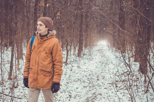 Mężczyznę idącego w zimowym lesie.