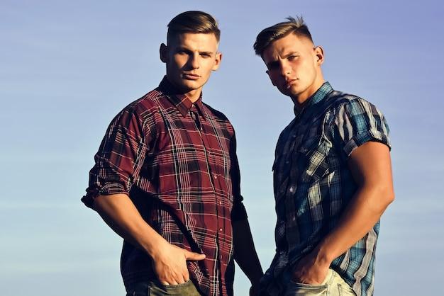 Mężczyźni bliźniacy w przyjaźni o zachodzie lub wschodzie słońca