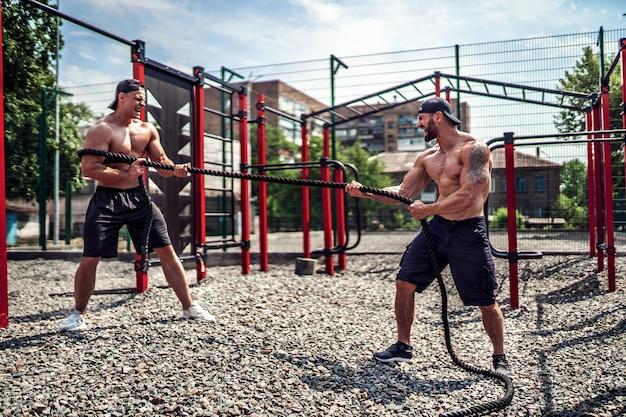 Mężczyźni ciężko pracują z liną na podwórku siłowni. trening na świeżym powietrzu. fitness, sport, ćwiczenia, trening i styl życia.
