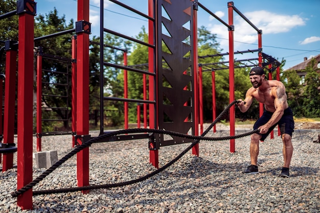 Mężczyźni ciężko pracują z liną, treningiem funkcjonalnym