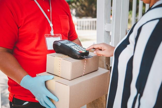Mężczyźni doręczyciele noszą higieniczne twarze i rękawice, dostarczają towary lub paczki, usługi dostawy