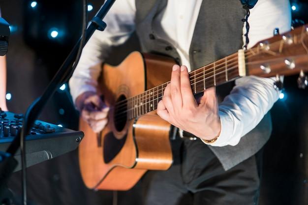 Mężczyźni grają na gitarze na koncercie.