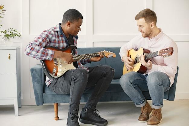 Mężczyźni grają na gitarze. pisanie muzyki. afrykańscy i kaukaski mężczyźni.