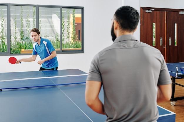 Mężczyźni grający w tenisa stołowego w salonie