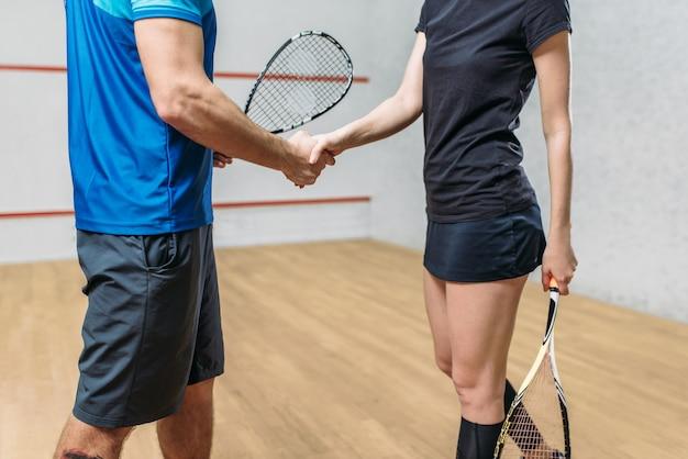 Mężczyźni i kobiety grający w squasha z rakietami podają sobie ręce.