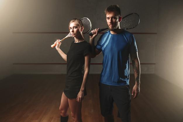 Mężczyźni i kobiety grający w squasha z rakietami