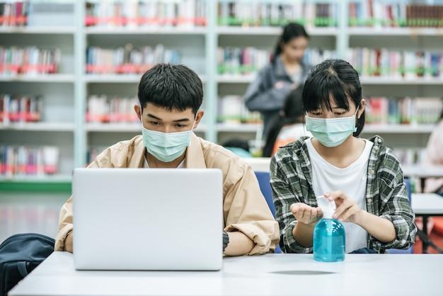 Mężczyźni i kobiety noszą maski i używają laptopa do wyszukiwania książek w bibliotece.