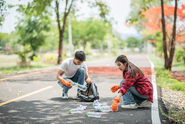 Mężczyźni i kobiety pomagają sobie nawzajem w zbieraniu śmieci.