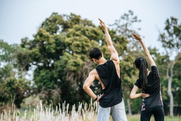 Mężczyźni i kobiety rozgrzewają się przed i po ćwiczeniach.