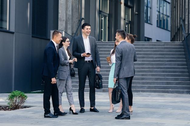 Mężczyźni i kobiety rozmawiają o biznesie. grupa sześciu młodych ludzi biznesu rasy kaukaskiej mężczyzn i kobiet spotykających się na zewnątrz budynku biurowego.