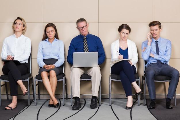 Mężczyźni i kobiety siedzą i czeka na rozmowę kwalifikacyjną