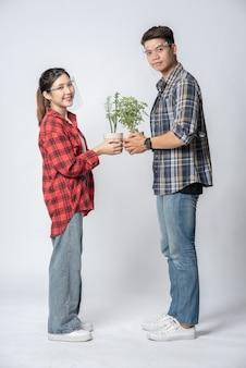 Mężczyźni i kobiety stoją i trzymają doniczki w domu