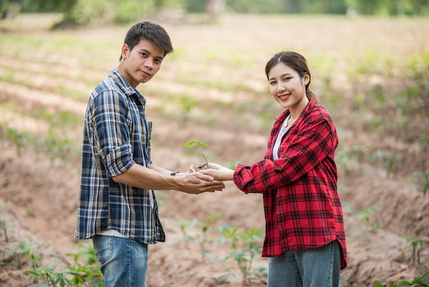 Mężczyźni i kobiety stojące i trzymające sadzonki.