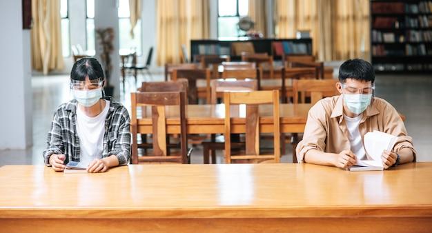 Mężczyźni i kobiety w maskach siedzą i czytają w bibliotece.