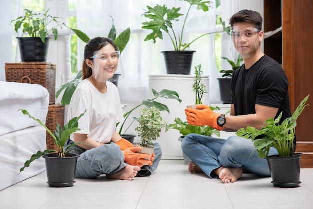 Mężczyźni i kobiety w pomarańczowych rękawiczkach siedzieli i sadzili drzewa w domu.