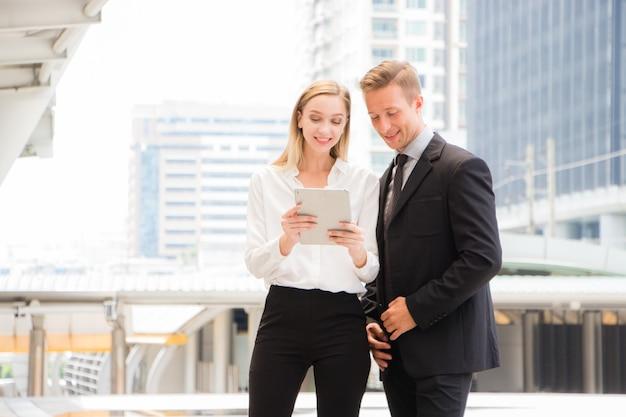 Mężczyźni i kobiety w ubraniach roboczych patrzą na tablety z uśmiechniętymi i szczęśliwymi twarzami.