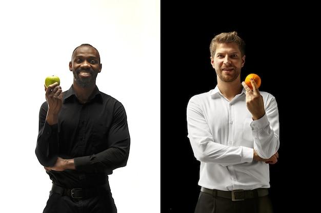 Mężczyźni jedzą świeże owoce na czarno-białym tle. szczęśliwi uśmiechnięci afro i kaukaski mężczyźni. koncepcja zdrowej żywności i diety