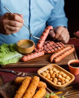 Mężczyźni jedzący grillowane kiełbaski z pieczoną ciecierzycą i krokiety