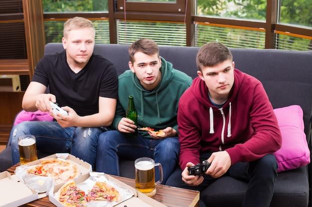 Mężczyźni kibice oglądają piłkę nożną w telewizji i piją piwo. trzech mężczyzn pije piwo i razem bawi się w barze