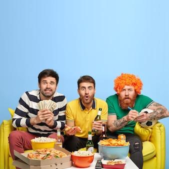 Mężczyźni kibice piłki nożnej, stawiaj zakłady, oglądając ekscytującą ligę, trzymaj banknoty dolara