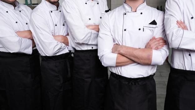 Mężczyźni kucharze stoją pewnie z założonymi rękoma w profesjonalnej kuchni. spełnia się marzenie o byciu szefem kuchni
