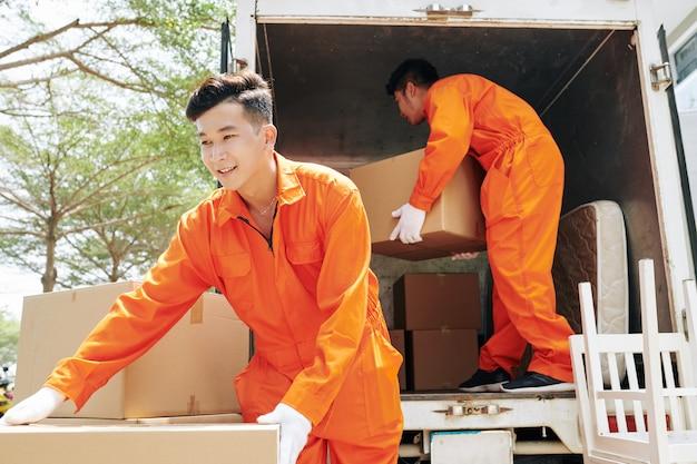 Mężczyźni ładują rzeczy gospodarstwa domowego