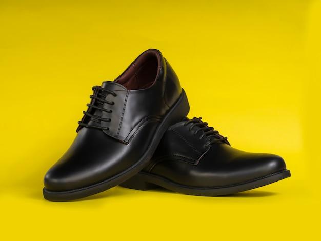 Mężczyźni moda czarne skórzane buty na żółtym tle.
