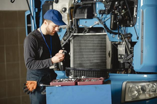 Mężczyźni naprawiają ciężarówkę. mężczyzna uczy naprawy samochodu. dwóch mężczyzn w mundurach