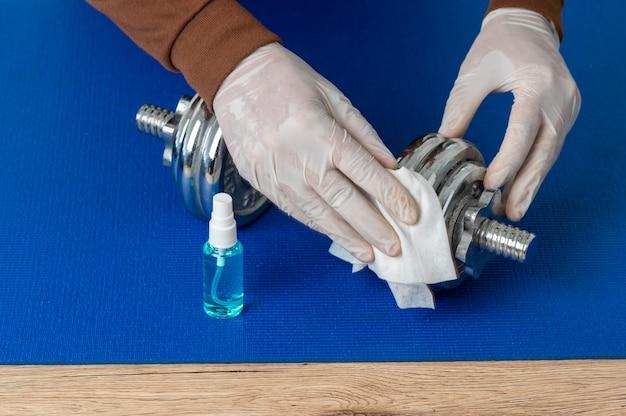 Mężczyźni noszą białe rękawiczki i używają alkoholu i szmatki do czyszczenia hantli, aby zapobiec wirusom.