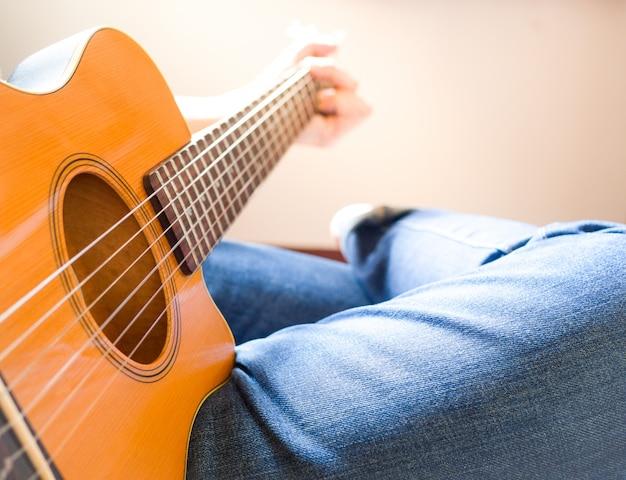 Mężczyźni noszą dżinsy i siedzą na gitarze akustycznej.