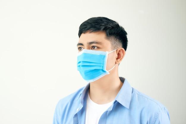 Mężczyźni noszą maski, aby zapobiec zanieczyszczeniu powietrza, białej ścianie, zamgleniu oraz pyłowi pm 2,5 i zanieczyszczeniu dymem w dużych miastach.