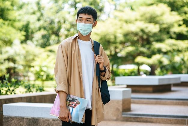 Mężczyźni noszą maski, książki i plecak na schodach.